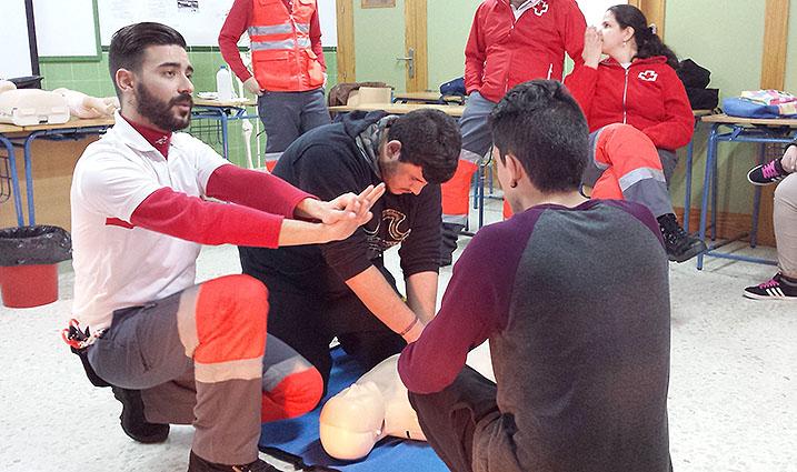 El técnico de Cruz Roja instruye a los alumnos sobre la forma de colocar las manos durante la aplicación de la RCP.